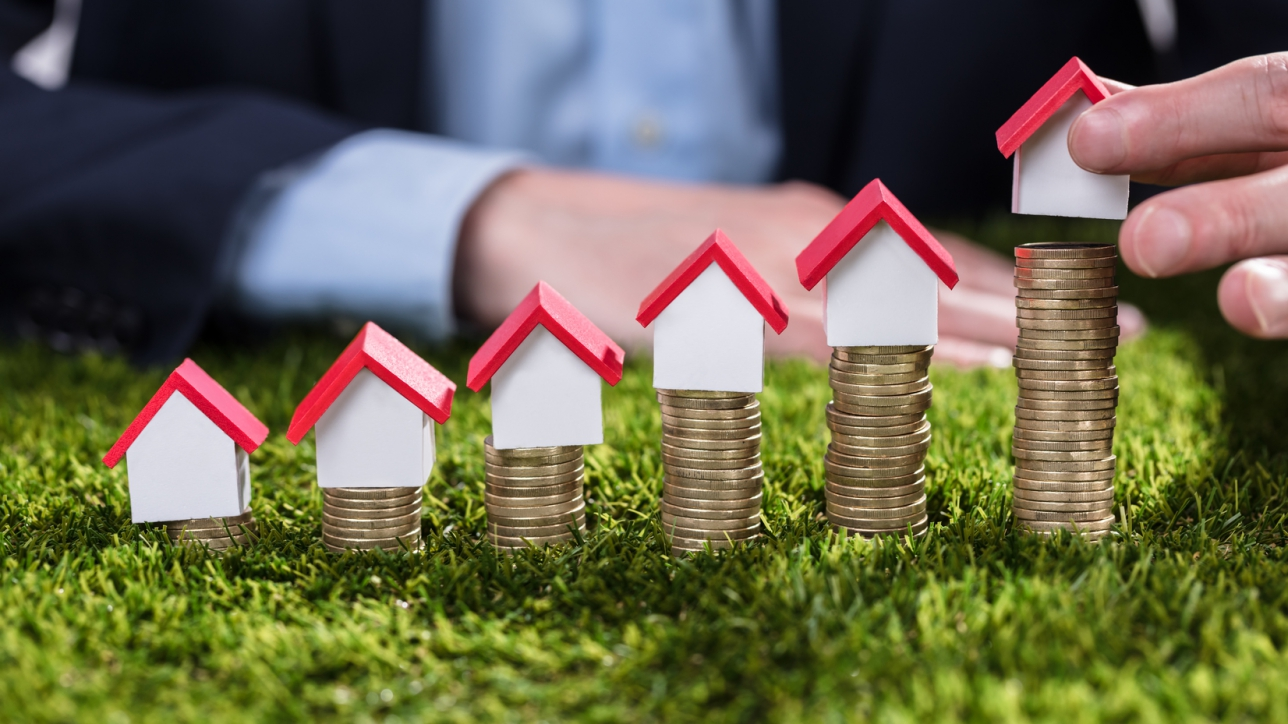 Businessperson's Hand Arranging House Model Over Stacked Coins On Green Grass